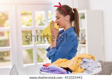A young beautiful housewife smell of freshly washed clothes