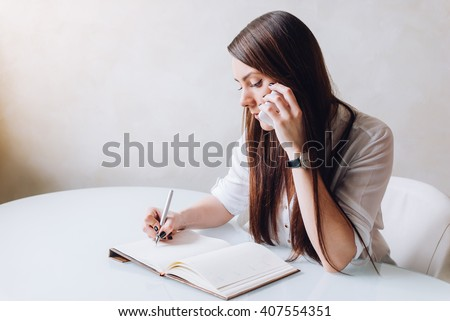A young beautiful receptionist and personal assistant is very serious. She is making a phone call and taking notices as a business woman - stock photo