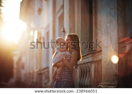 A young beautiful slim woman in a blue dress with her little cute baby walking around the old town on a sunny summer day. - stock photo