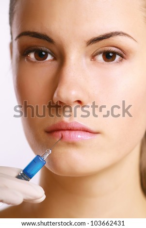 A young beautiful woman having an injection isolated on white background - stock photo