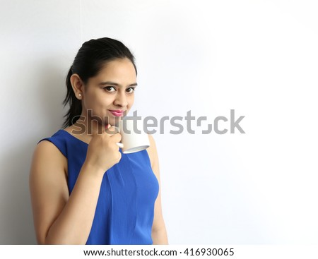 A Young beautiful woman holding cup of tea or coffee isolated on white background. - stock photo