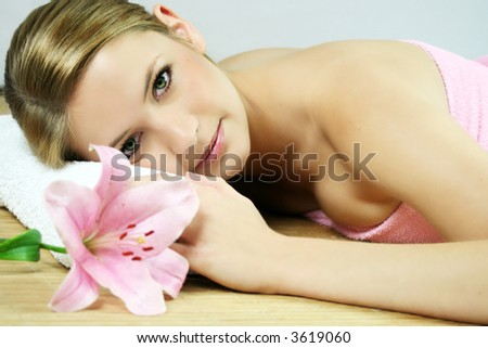 a young beautiful woman is relaxing in spa - wellness with a flower lily - stock photo