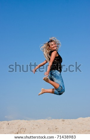 a young beautiful woman  jumps on a sand-pit  on a background blue sky