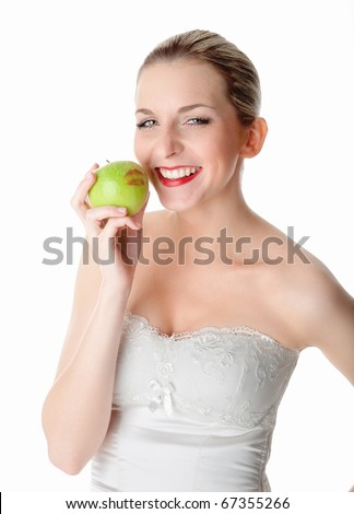 A young, beautiful woman kisses a green apple