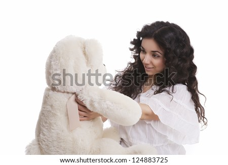 a young beautiful woman looks at a teddy bear - stock photo