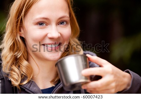 A young beautiful woman outdoors on a camping trip taking a drink - stock photo