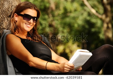 A young beautiful woman reading in the park and smiling - stock photo