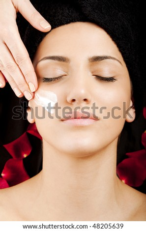 A young beautiful woman receiving moisturizing cream on cheek - stock photo