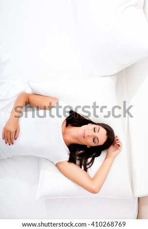 A young, beautiful woman relaxing in the bed at home - stock photo