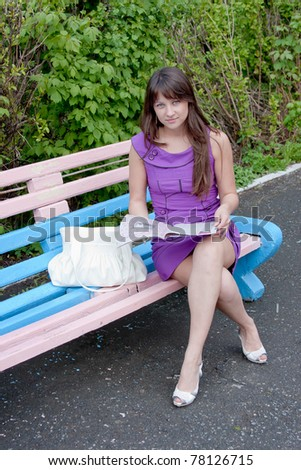 a young beautiful woman sits in a park on a bench with a newspaper in hands