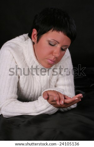 A young beautiful woman wearing wearing white sweater lying on the bed covered with black cloth - stock photo