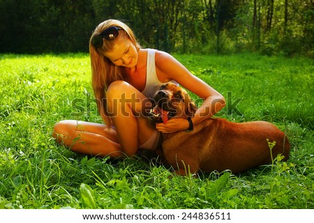 A young beautiful woman with blonde hair is playing with a mastif dog in a backyard with green grass - stock photo
