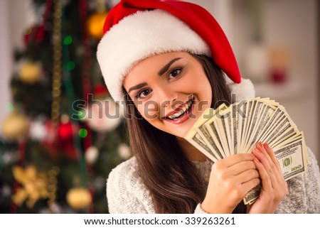 A young beautiful woman with many money celebrating Christmas at home - stock photo