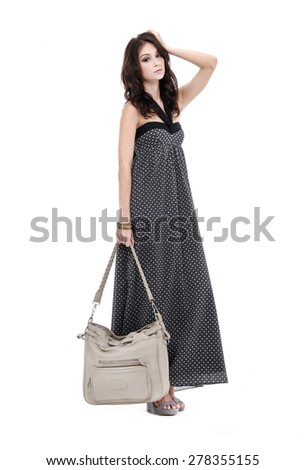 a young beauty in black dress with bag posing-black background - stock photo