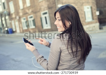 A young beauty posing over an urban city with earphone and phone