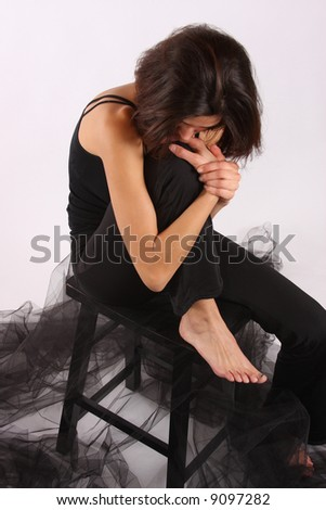 A young bereaved female sitting alone on a chair