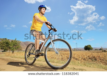 A young biker riding a mountain bike on a sunny day, Macedonia - stock photo