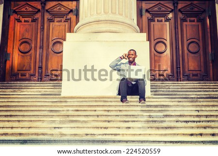 A young black business man is sitting on stairs of old fashion style office building door way, smiling, working on laptop computer, talking on his mobile phone. The Way to Success. - stock photo