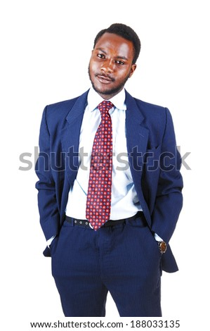 A young black business man standing in a blue suit and tie with his hands in his pocket for white background.  - stock photo