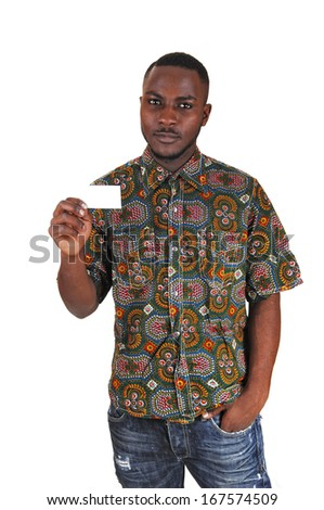 A young black man in a colorful shirt and jeans holding a white business card in his hand for white background.  - stock photo