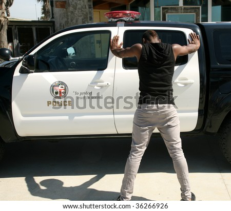 a young black man is up against a police car with his feet spread - stock photo