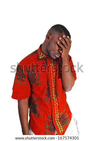A young black man standing for white background with his hand on his face, looking very sad.  - stock photo