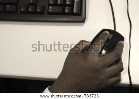 A young black woman's hand maneuvers the mouse at the keyboard.