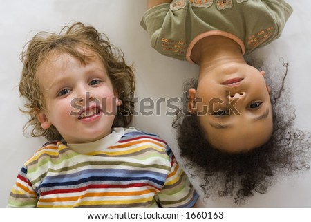 A young blond boy and a beautiful mixed race little girl looking up into the camera