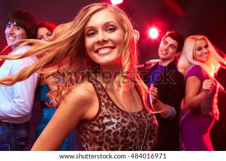 A young blond dancing, looking at camera and smiling against her four friends