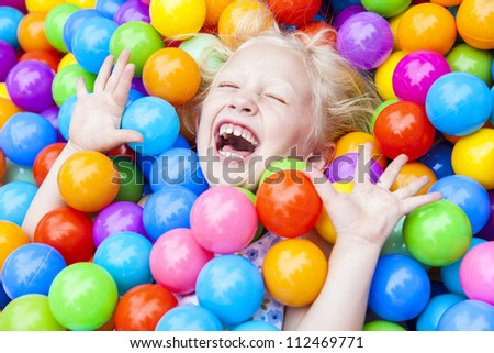 A young blond girl child having fun laughing playing with hundreds of colorful plastic balls - stock photo