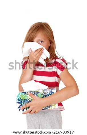 A young blond girl, holding a box of tissue's and blowing her nose, isolated for white background.