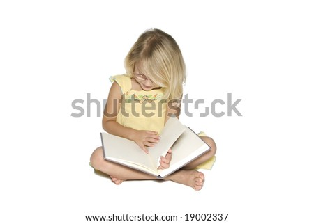 A young blond girl sitting cross legged while reading a textbook.  Isolated on a white background