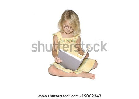 A young blond girl sitting cross legged while reading a textbook.  Isolated on a white background - stock photo