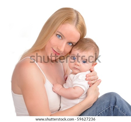 A young blond mother is holding her newborn baby on a white background. They are wearing white clothes and they are hugging. Use it for a parenting, happiness or security concept - stock photo