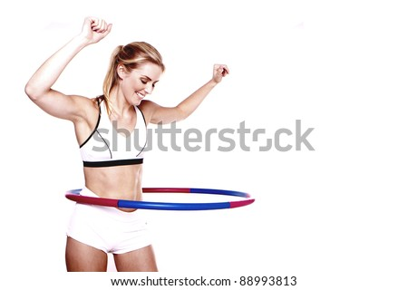 A young blond woman doing exercise with a hula-hoop.Fitness woman.
