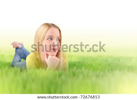 A young blond woman is laying in the grass looking up in the sky. There is white copyspace to add your message. Use it for an environment or green concept. - stock photo