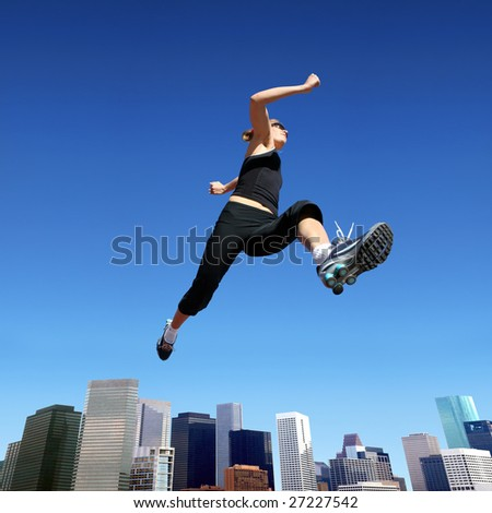 A young blond woman jumping high above downtown - stock photo