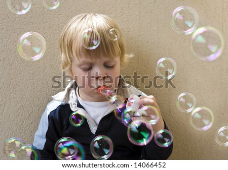 A young blonde boy blowing bubbles