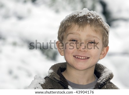 a young blonde boy has fun in the snow