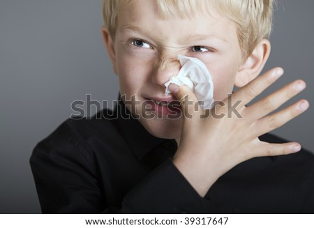 a young blonde boy with a cold and a tissue blowing his nose