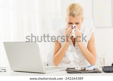 A young blonde business woman at her workplace at an office desk in front of laptop, shaking her nose into a handkerchief ready to take the pills. - stock photo