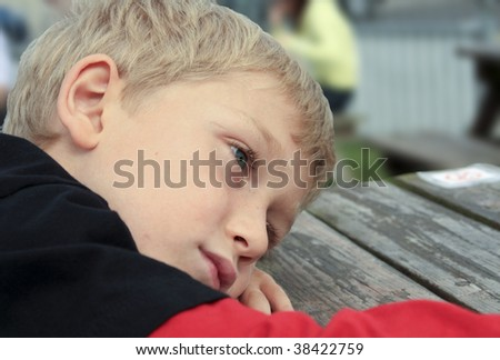 a young blonde child sitting pensively thinking head on table