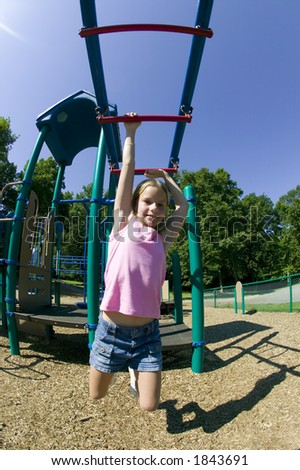 A young blonde girl palys on the monkey bars at a local park. - stock photo