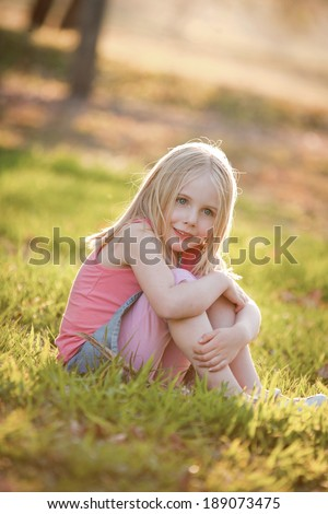 A young blonde girl sitting on the grass in the back light in summer.  She is sitting down smiling and looking at the camera.   - stock photo