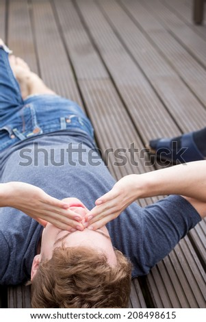A young blonde male model is lying on his back and is dealing with problems