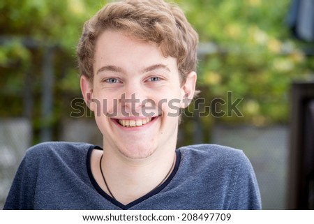 A young blonde male model is smiling into the camera with a nice modern background - left