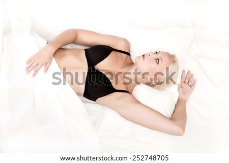 A young blonde woman laying in bed. - stock photo