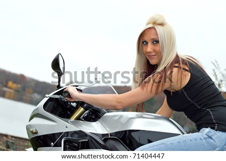 A young blonde woman poses on her motorcycle. - stock photo