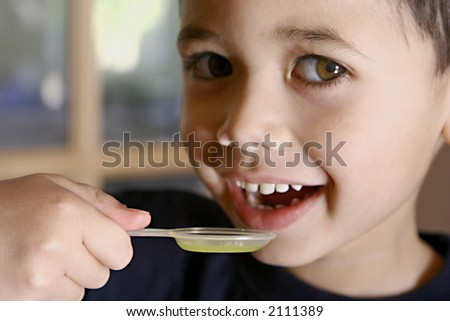 A young boy about to have his medicine in a spoon. - stock photo