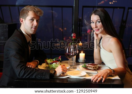 A young boy and a beautiful girl sitting at the table - stock photo